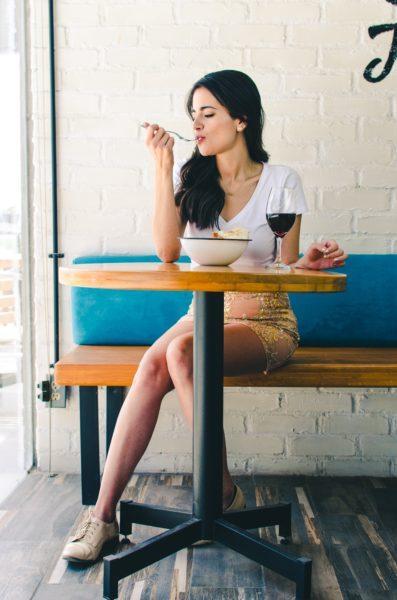 Junge Frau genießt ihr Essen bei einem Glas Wein