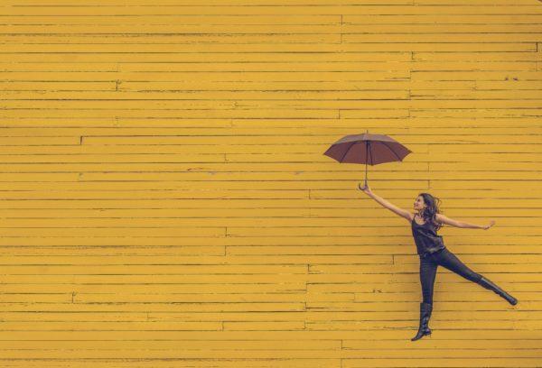 Mädchen mit Regenschirm vor gelbem Hintergrund